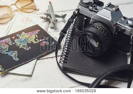 Retro camera and map on wooden table Travel concept
