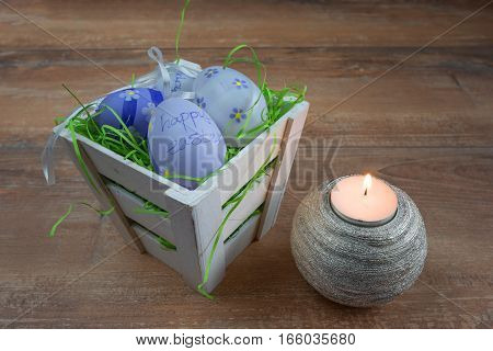 Easter small basket with colored eggs and a burning candle on brown wooden board.