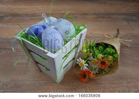 Easter small basket with colored eggs and a bunch of spring flowers on brown wooden board.