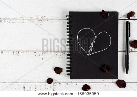 Red broken heart with dried rose petal and notebook on white wooden background