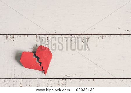 Red broken heart on white wooden background with copy space