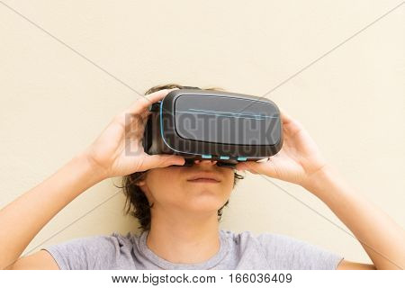 Teenager wearing and holding VR virtual realty glasses