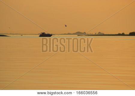 distant motorboat at the orange sunset light