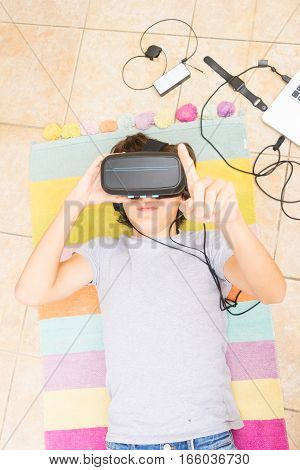 Teenager boy wearing VR virtual realty glasses in home