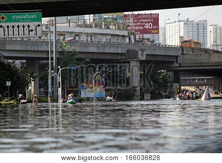 Thailand Bangkok - November 2011: local residents moving on the water flooded the streets of the city during the flooding in Bangkok
