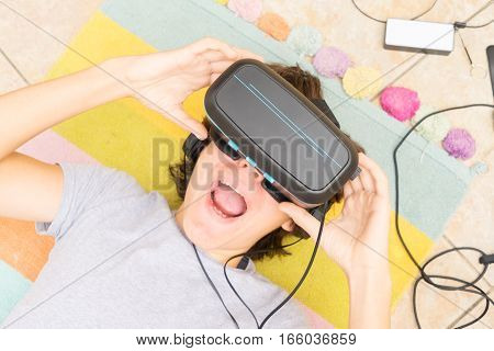 Teenager wearing VR virtual realty glasses in home close up