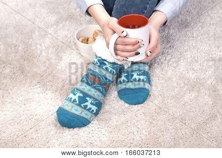 Female hands holding herbal tea while sitting on floor