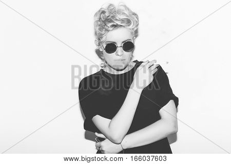 Stylish fashion sexy blonde bad girl in a black t-shirt and rock sunglasses. Dangerous rocky emotional woman smoke. Black and white toned. White background, not isolated
