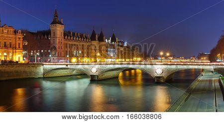 Panorama of Conciergerie and Illuminated bridge Pont au Change at night, Paris, France