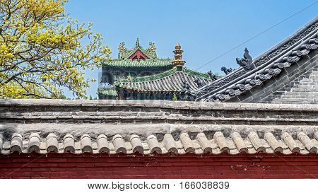 China the Shaolin Monastery. The roofs of the buildings of the temple against the blue cloudless sky.