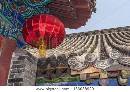 China the Shaolin Monastery. Bright colored lantern made of natural silk in China against the background of the roof of one of the halls.