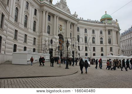 VIENNA, AUSTRIA - JANUARY 3 2016: Michaelerplatz square in Vienna at day time facing the Hofburg complet entrance and people around