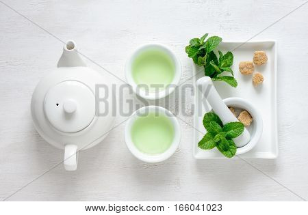 Fresh mint tea concept, top view tea pot and cups