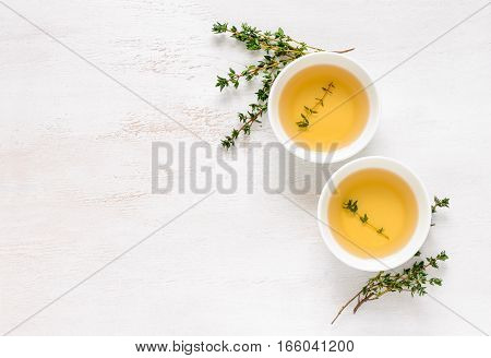 Thyme herbal tea view from high angle on two cups with tea space for a text