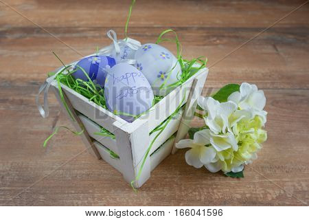 Easter small basket with colored eggs and a white flower on brown wooden board.