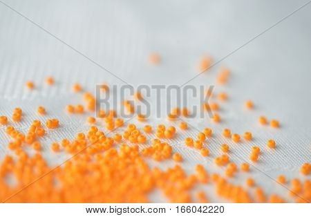 Seed Beads Of Orange Color On Textile Background