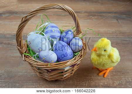 Easter wicker basket with colored eggs and a small chicken on brown wooden board.