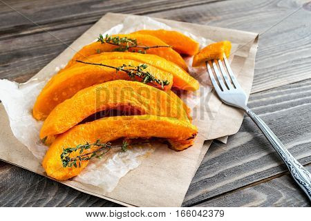 Slices of ripe roasted pumpkin with a sprig of thyme lying on the kitchen wooden table. Close-up