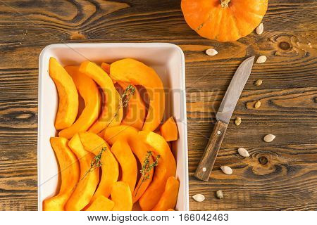 Slices of ripe pumpkin with a sprig of thyme lay in the baking dish on the kitchen wooden table dark background
