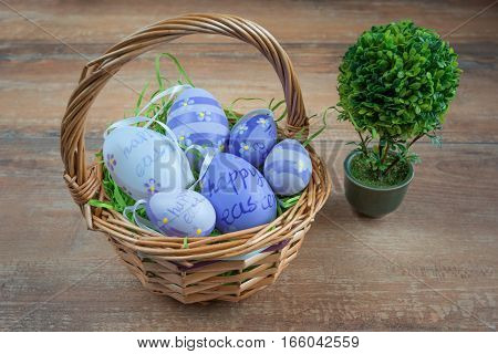 Easter wicker basket with colored eggs and a small bonsai on brown wooden board.