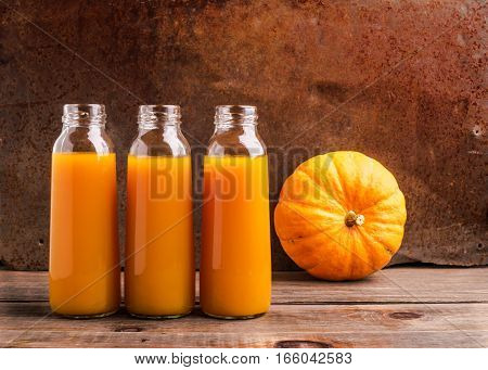 The fresh juice of ripe pumpkin bottled in small glass bottles. Dark wooden background