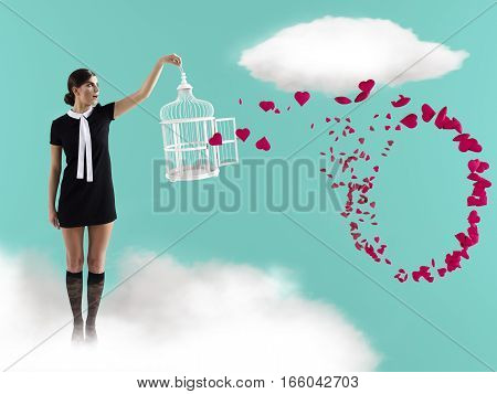 woman standing on cloud with cage captureing flying hearts.