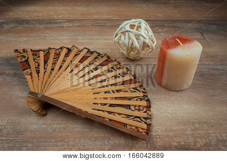 Brown wooden fan, red-white candle and white ball on brown wooden board.