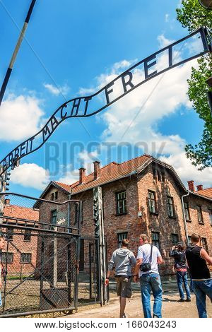 AUSCHWITZ-BIRKENAU CONCENTRATION CAMP, KRAKOW, POLAND - CIRCA JUNE 2012: View of entrance of the camp with famous inscription Arbeit Mach Frei