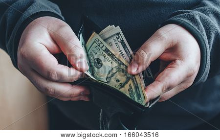Hands holding us dollar bills and open wallet or pouch.  Man counting money, economy concept, allocation of money. Toned picture