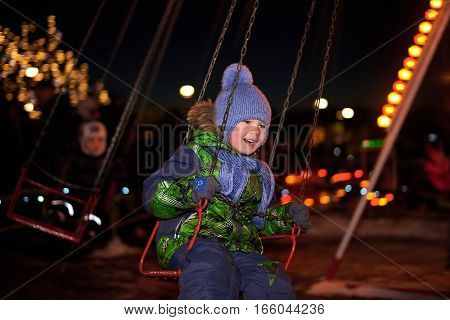 Boy swinging on a swing in the Christmas night