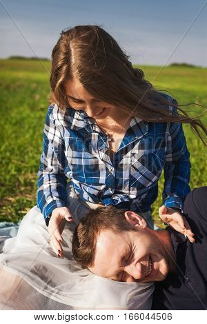 young girl in checkered shirt sitting on the grass. boy put his head on the girl's knees. They are happy and laughing