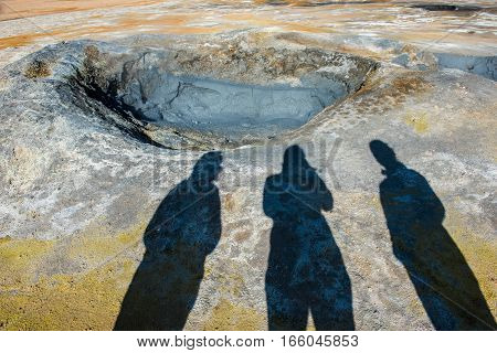 Mud-pots in the geothermal area Hverir colorful sulphurous mud springs cracked mud in Namafjall shadows of tourists