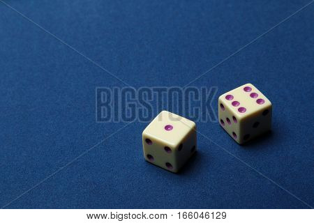 Dice from an ivory on dark blue cloth