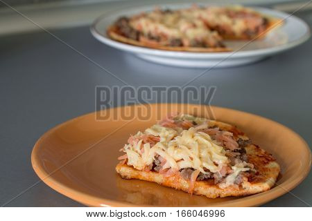 Frittata with tomato sauce, carrot, fried minced beef and cheese on white plate.