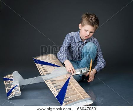 Pre-teen boy holding a wooden plane model. Kid playing with real handmade plane glider.