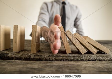 Businessman halting the domino effect inserting his hand between falling and upright wooden blocks in a close up conceptual image. poster