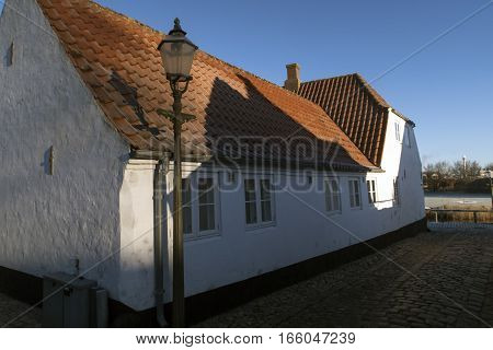 Old white house with a street lamp in Ribe Denmark.