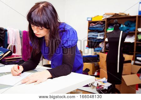 a female fashion designer is working on a new piece of clothing in her somewhat chaotic studio. in this shot, she is creating some sketches.