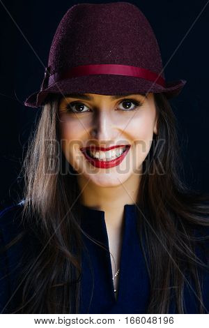 Happy smiling female model in elegant hat on gray background. Portrait of the girl in studio.