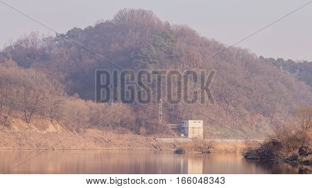 Landscape of river with a storage shed and a electrical tower in the background