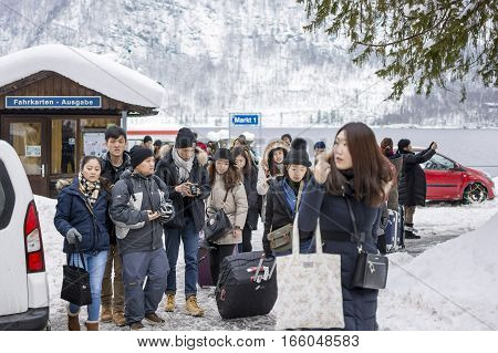 HALLSTATT AUSTRIA - JANUARY 09 2017 : Group of Chinese Tourists in the Port Coming to Hallstatt Across the Moutain Lake by Boat - Water Bus