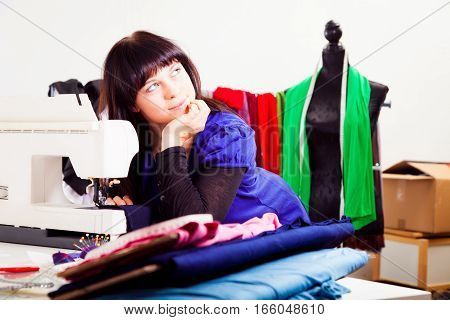a female fashion designer is working on a new piece of clothing in her somewhat chaotic studio.