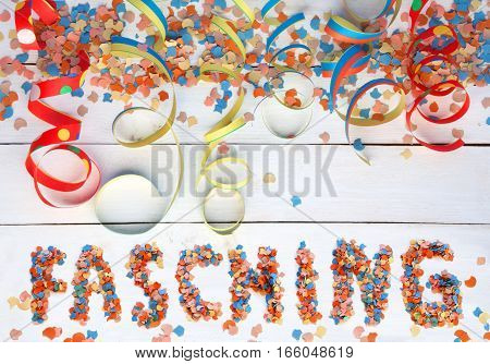 Carnival background with colorful text and streamers on white wooden board