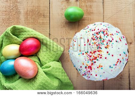 Easter cake and painted eggs on wooden background. Top view.