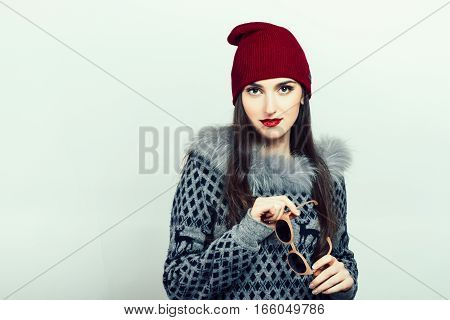 Beautiful girl in the red hat on the grey background. Valentine day. Winter style.