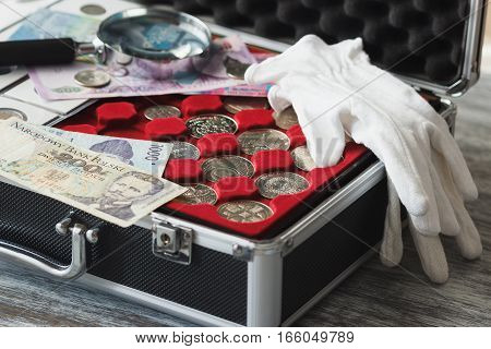 Different collector's coins and banknotes in the box with a magnifying glass soft focus background