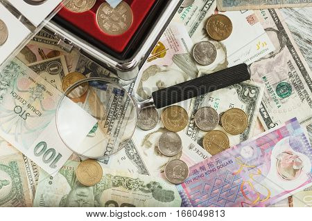 Different collector's coins and banknotes with a magnifying glass soft focus background