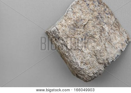 Piece of schist rock isolated over grey background. Metamorphic rock coming from Malaga mountains Spain