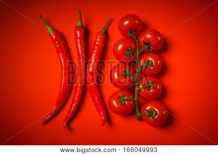 spicy peppers and small tomatoes on a red background