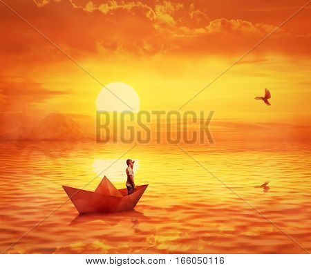 Silhouette of a lonely boy in a paper boat sailing lost in the ocean against orange sunset sky and a pigeon flying to find the shore. Adventure and journey concept searching for help.